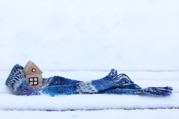 warming things for comfort/ small wooden house wrapped in a scarf on the background of snowy landscape