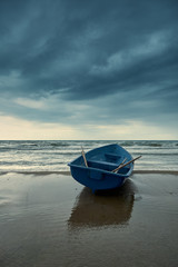 Small blue rowboat on beach