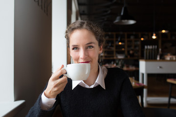 Smiling young woman drinking coffee while sitting in the cafe