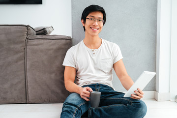 Asian man sitting with coffee and tablet