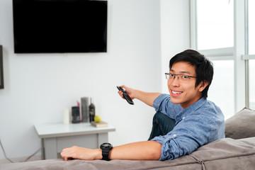 Young asian man in shirt watching tv