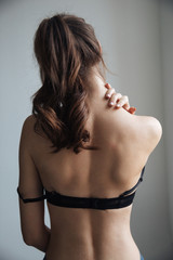Back view of young naked woman in bra
