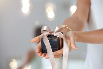 Shot of female hands holding a small gift box.
