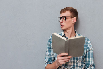 Young student in glasses with book