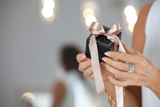 Beautiful female hands holding a small gift box.