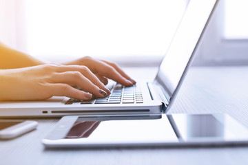 Woman's hands using laptop at the office