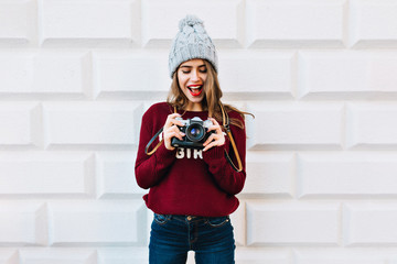 Beautiful girl in marsala sweater on grey wall background. She wears knitted hat, is astonished looking at camera in hands