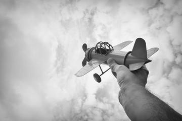 close up photo of man's hand holding retro airplane