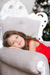 Little girl in a red dress near a Christmas tree at home
