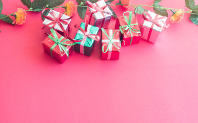 Christmas gift box with green leaves on red color background for