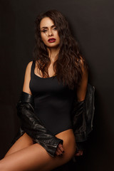 Seductive and shameless young woman with sexy shapely forms, loose wavy hair, vinous lipstick and slim figure is posing in the black body leather and jacket, studio photoshoot, dark background