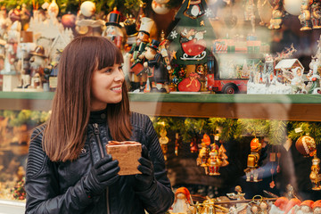 beautiful woman holding christmas present in front of christmas toys shop