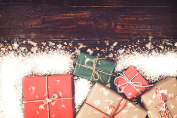 Christmas gift boxes with snowfall on rustic wooden board with copy space. top view on wood table. vintage color effect.