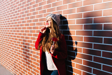 Attractive brunette girl with long hair on wall background outside. She wears knitted hat, red coat. Holds lollipop red lips. Smiling with closed eyes to sunshine