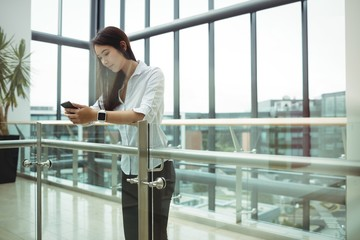Businesswoman leaning on railing and using mobile phone