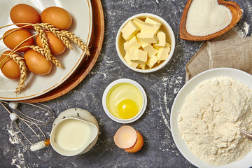 Ingredients for baking. Baking background with eggs, flour and pitcher milk, butter. Top view. Rustic style.