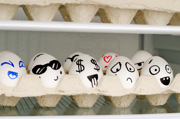 Eggs with painted emotions in a tray on a shelf in the refrigerator
