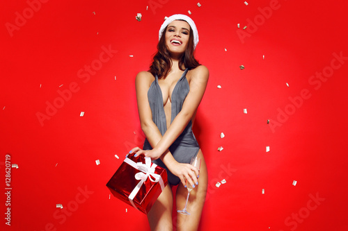 23700e6885c71 ... girl model stands on red background in sexy bathing suit bikini and a Christmas  Santa hat.on the background of flying golden candy.advertising photo.