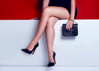 Fashion woman legs in dress black purse and high heels shoes