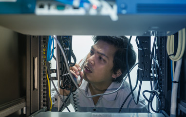 Man troubleshooting in data centre with consult by telephone