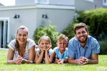 Front view of happy family lying in yard