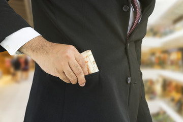 scene of businessman pull money from pocket suit on blur departm - can use to display or montage on product