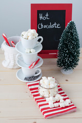 Hot chocolate station with. cups, mini marshmallow, candy canes. A decorative tree and a chalkboard sign