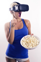 Attractive young woman watching movies and clips with VR glasses an eating pop corns