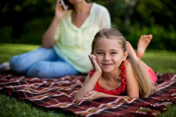 Girl lying on blanket while mother sitting in background