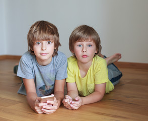 Two  kids lying on wooden floor with smarth phone