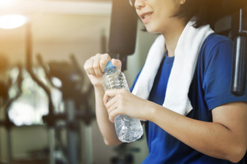 Asian woman holding bottle of water after  workout.