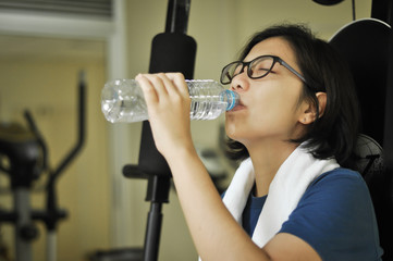 Asian woman drinking water after her workout.