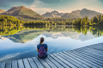 Alone young girl sitting and resting on the wooden path near by beautiful blue lake and clear big mountains. Original wallpaper from summer morning