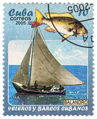 Yacht and fish on postage stamp