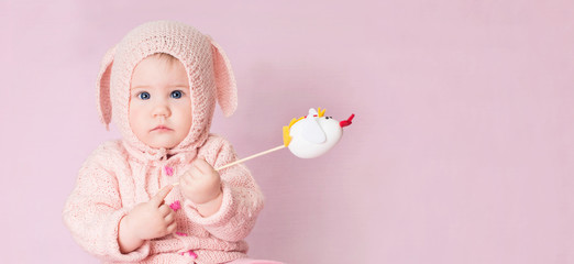 Closeup portrait of cute baby in knitted costume of Easter bunny