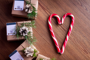 Decorated gift boxes and candies on the wooden background.