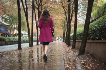 Businesswoman with diary walking on wet pedestrian walkway