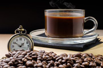 Coffee time concept with vintage pocket watch on coffee beans ba