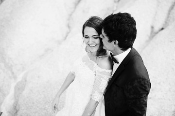 beautiful and happy groom and bride standing together outdoors