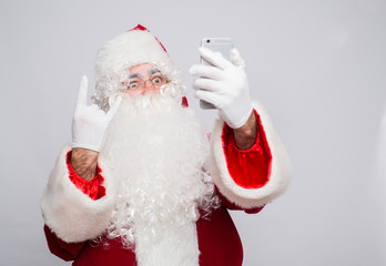 Santa Claus makes a selfie on white background showing rock gesture
