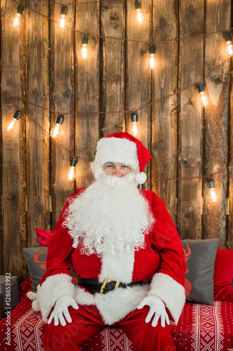 Quot traditional santa claus sitting on the couch and having a