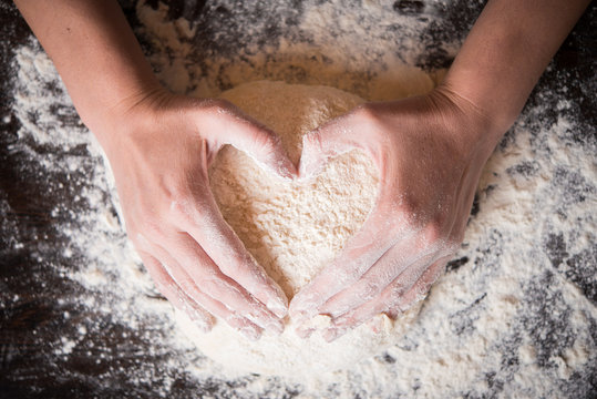 Female hands holding dough in heart shape