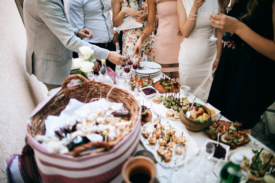 friends drink alcohol and eat snacks and talk at the celebration of the wedding. communication concept