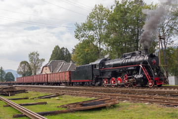 Retro locomotive with freight cars at the station