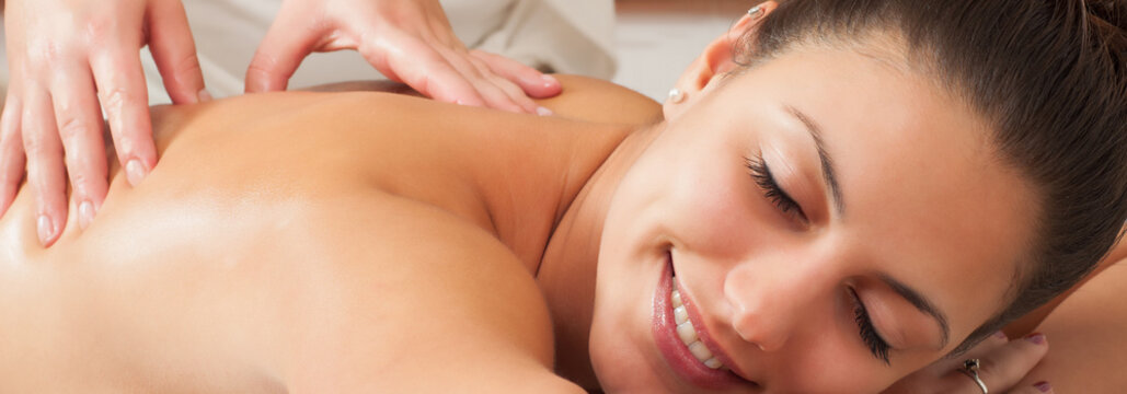 Girl getting back massage in massage salon, health spa