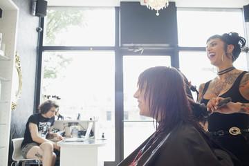 A hair dresser styling a customer's hair.