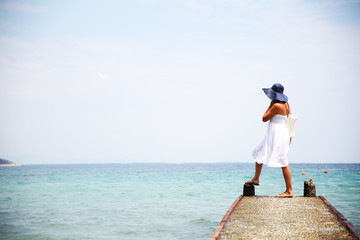 Woman in white summer dress enjoying beach and summer sunny day