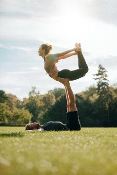 Flexible young couple doing acroyoga outdoors