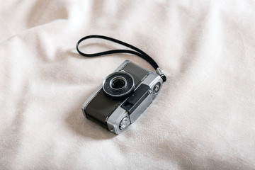 Vintage camera on soft white plaid cover background.