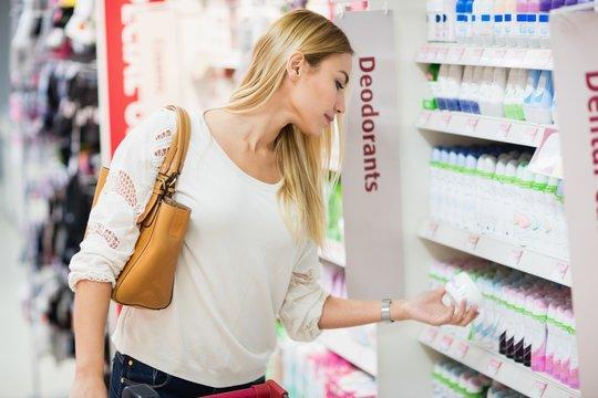 Side view of woman choosing deodorant